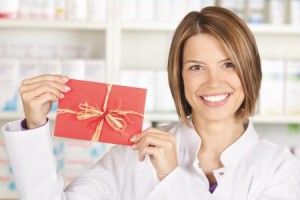 Smiling pharmacist showing a red card at the drugstore